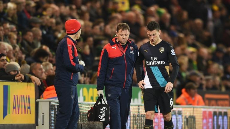 Laurent Koscielny leaves the pitch at Carrow Road after injuring his hip