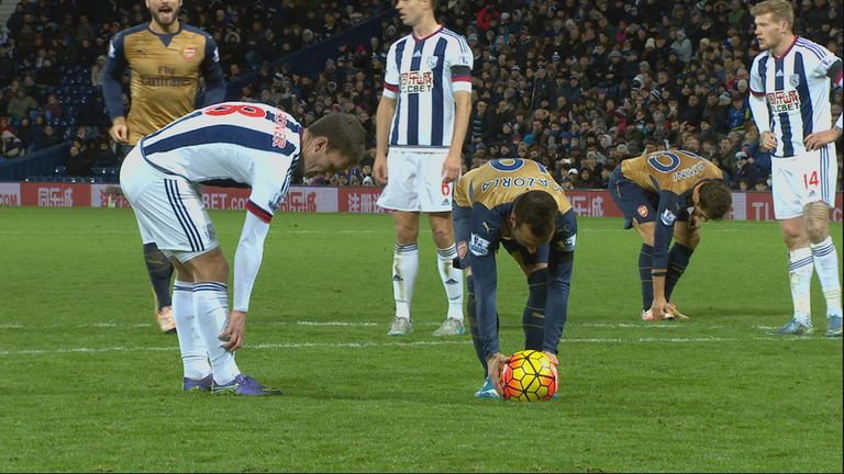 Craig Gardner tries to delay the taking of Santi Cazorla's penalty.