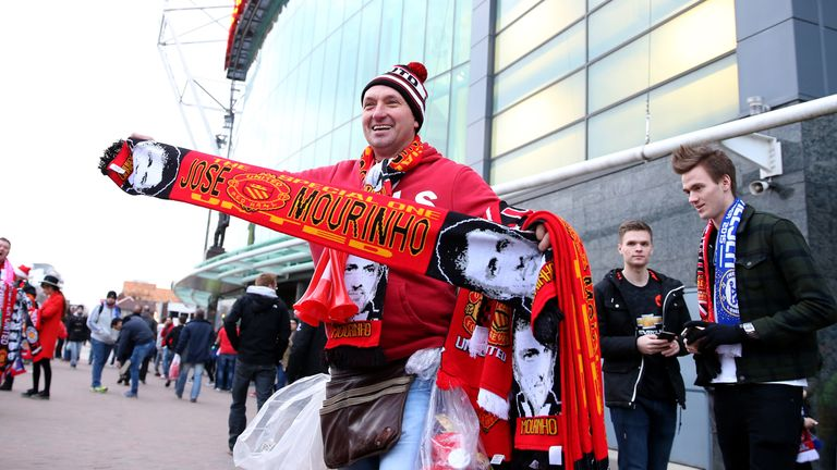 A street trader sells Jose Mourinho Manchester United scarves before the match