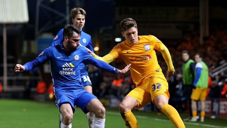 Adam Reach of Preston holds off pressure from Peterborough's Michael Smith