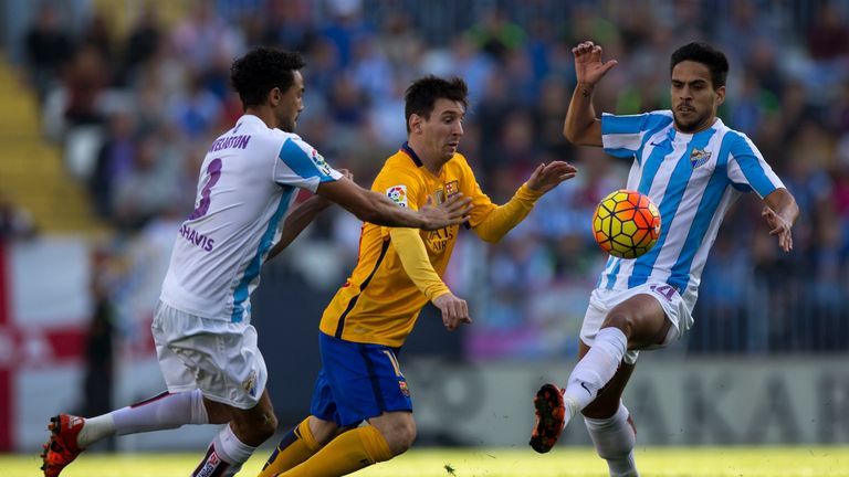 Lionel Messi (2ndL) of Barcelona tries to evade the challenges of Wellington Robson (L) and Recio of Malaga
