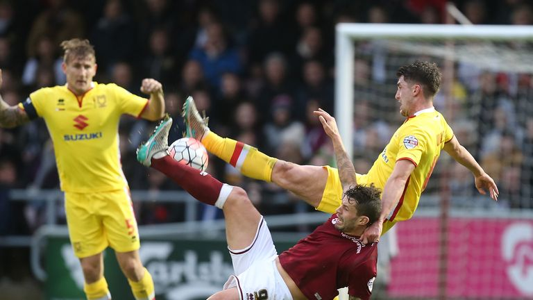 Northampton Town's Marc Richards contests the ball with Joe Walsh of Milton Keynes Dons at Sixfields Stadium