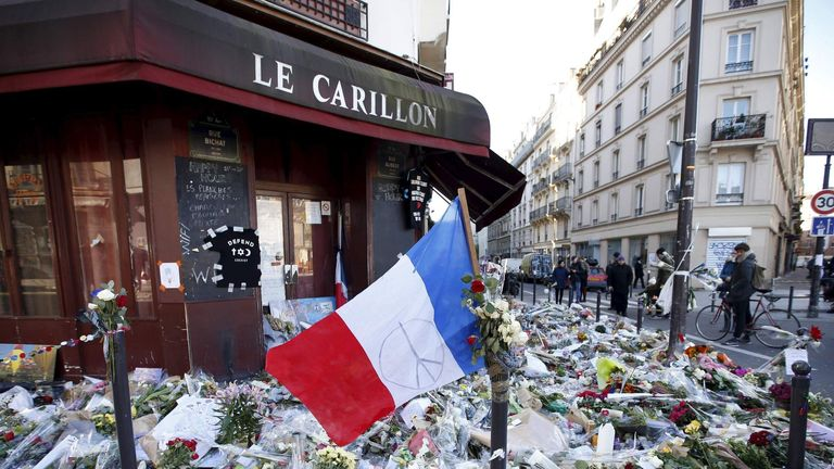 A French flag flies over flowers, candles and messages in tribute to victims following the November terrorist attacks in Paris