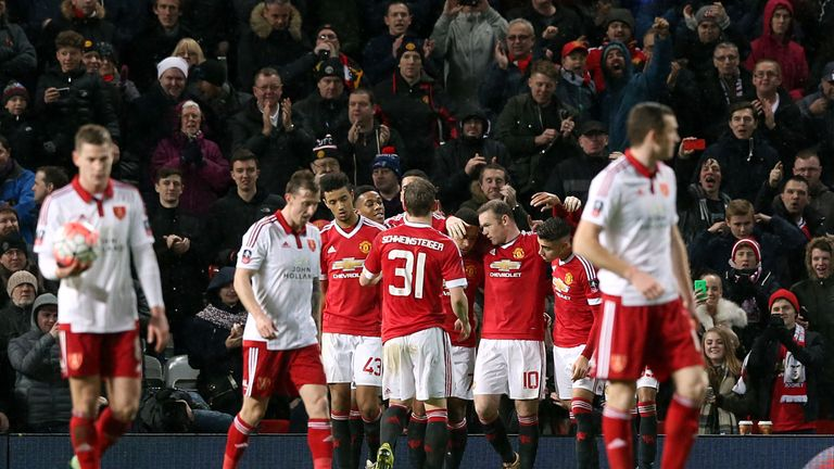 Sheffield United players stand dejected as Manchester United's Wayne Rooney celebrates scoring the hosts' winner on Saturday