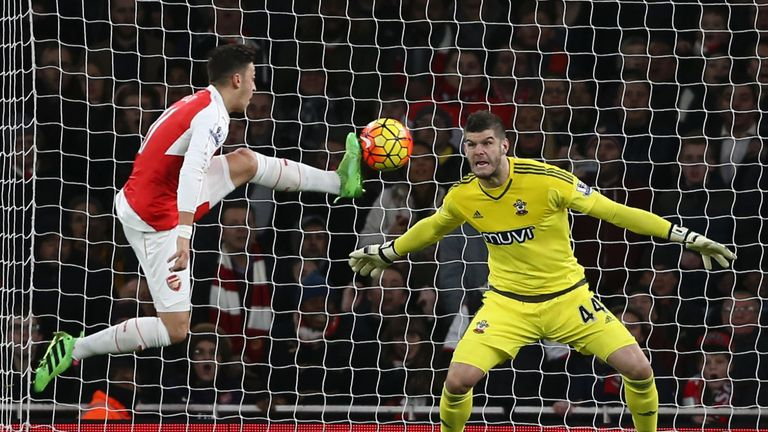 Arsenal's Mesut Ozil (left) tests Fraser Forster (right) but the Southampton goalkeeper makes the save