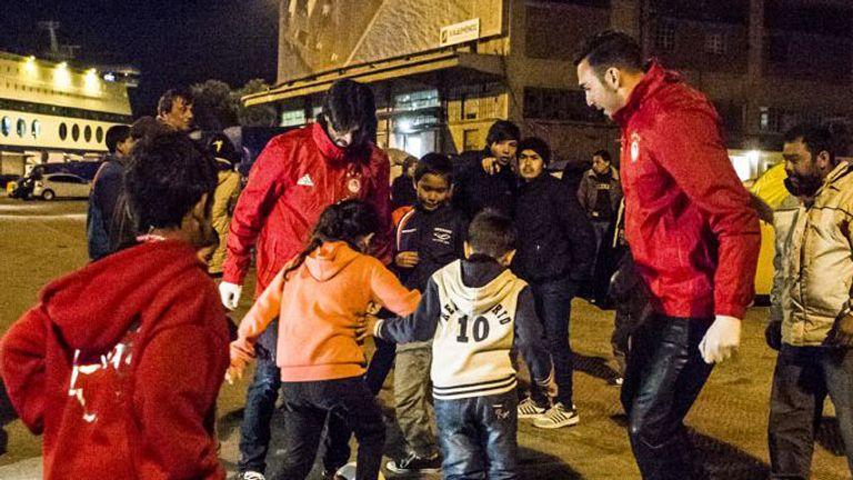 Roberto Jimenez and Chori Dominguez play football with refugee children