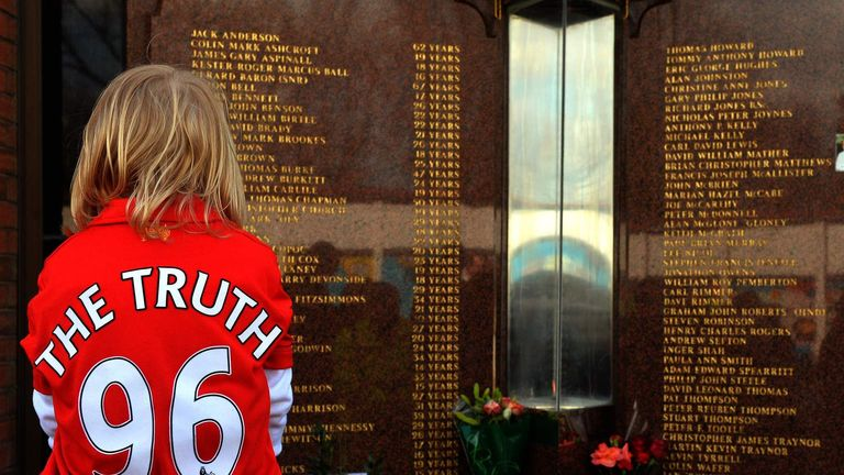 A Liverpool supporter pays her respects at the Hillsborough memorial