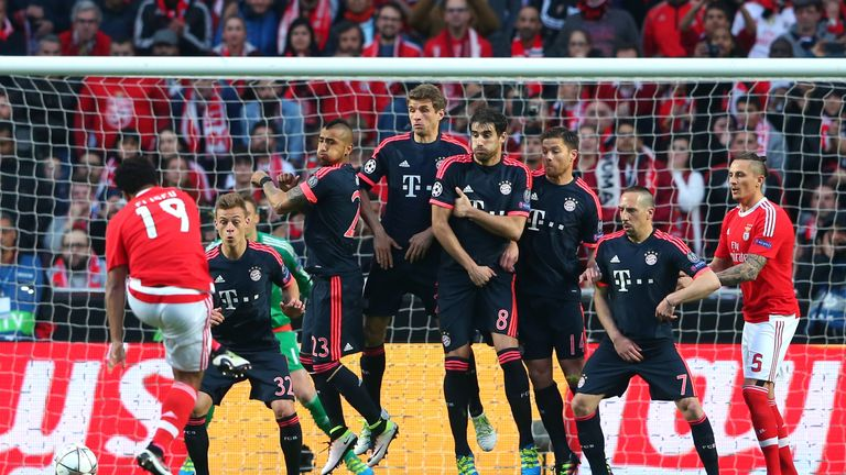 Bayern Munich players jump in the wall to defend a free kick