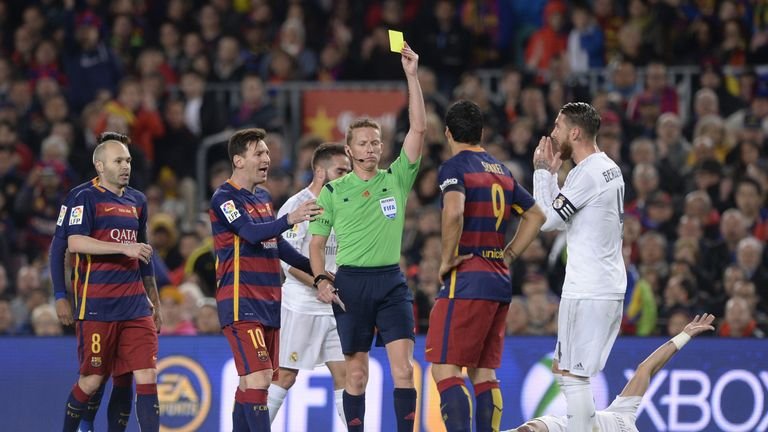 Barcelona forward Luis Suarez (second right) is given a yellow card