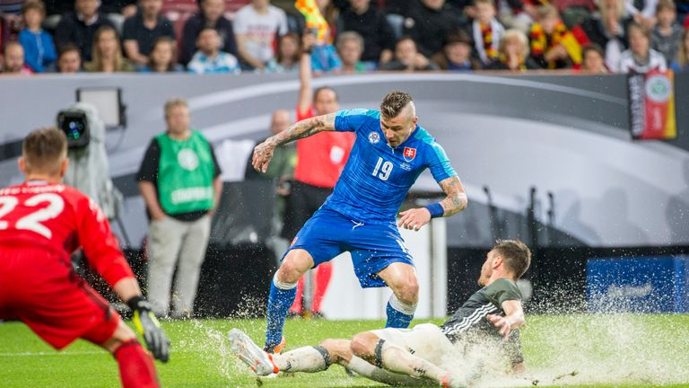 Jonas Hector (R) of Germany is challenged by Juraj Kucka of Slovakia during a storm-hit friendly