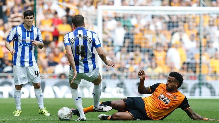 Hull City midfielder Tom Huddlestone tackles Sheffield Wednesday defender Sam Hutchinson (2L)