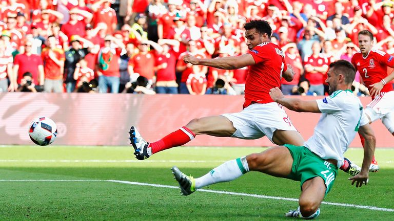 Northern Ireland's Gareth McAuley (front) can only divert a cross from Wales' Gareth Bale into his own net