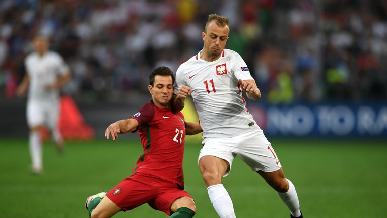 Kamil Grosicki of Poland (right) is tackled by Portugal's Cedric Soares