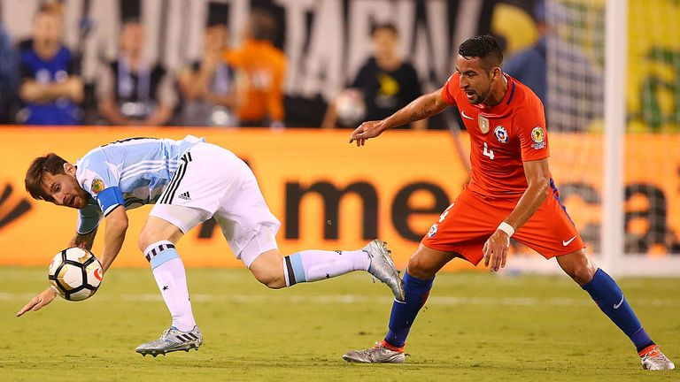 Lionel Messi  is tripped by Mauricio Isla (R)