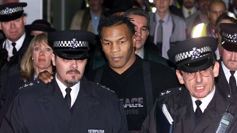 Police guide Mike Tyson through Heathrow after Home Secretary Jack Straw allowed him to enter England