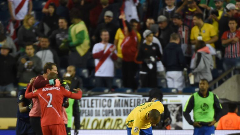 Members of Peru's national team celebrate their victory as Brazil's Miranda comforts team-mate Renato Augusto