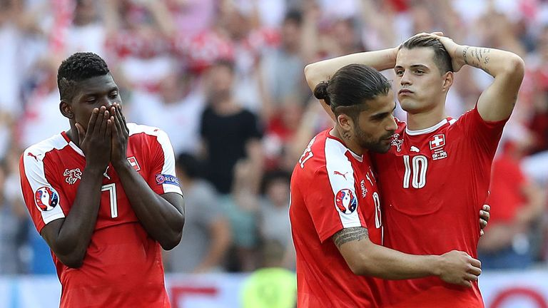 Xhaka (R) reacts after missing a vital penalty for Switzerland