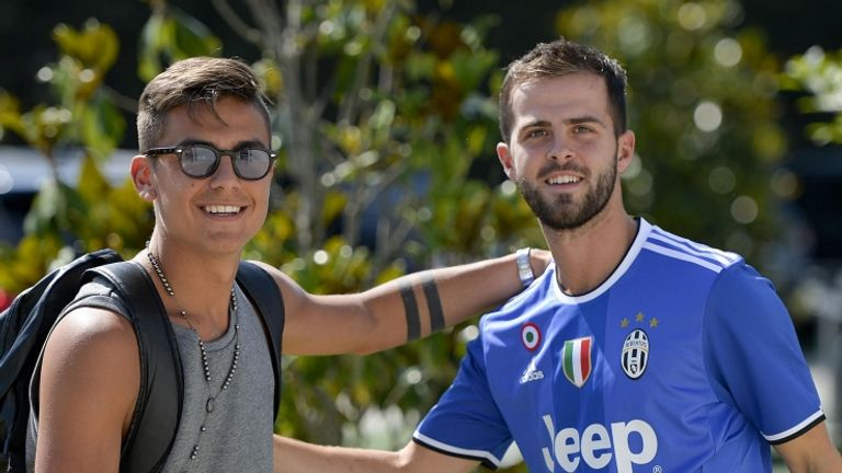 Miralem Pjanic (right) is greeted by new Juventus team-mate Paulo Dybala