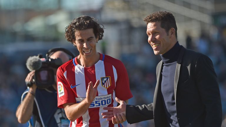 A relaxed Diego Simeone (right) shares a joke with midfielder Tiago (left)