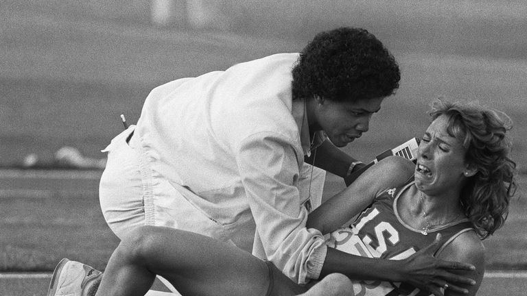 Decker is comforted by a track official after falling during the 3000m final in Los Angeles