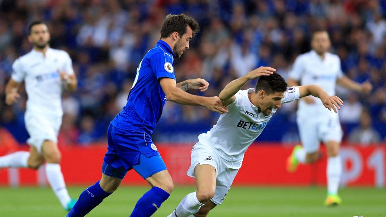 Christian Fuchs (L) and Swansea's Federico Fernandez battle for the ball