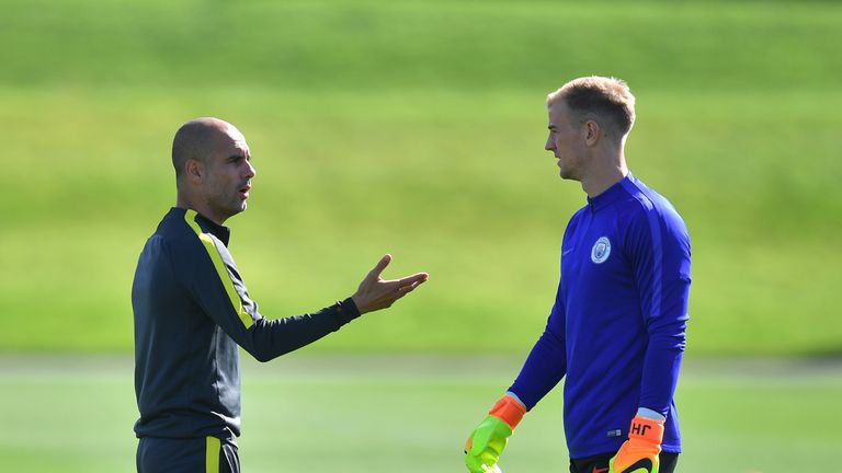 Manchester City manager Pep Guardiola talks to Hart in pre-season