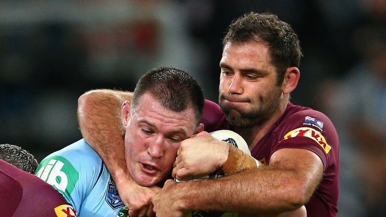 Paul Gallen of the Blues is tackled by Maroons captain Cameron Smith