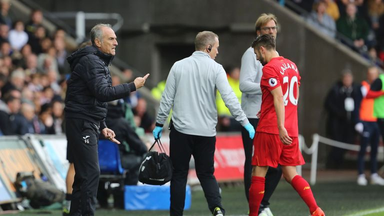 Liverpool and England midfielder Adam Lallana goes off injured in the first half