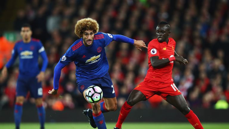 Marouane Fellaini (left) challenges Sadio Mane at Anfield