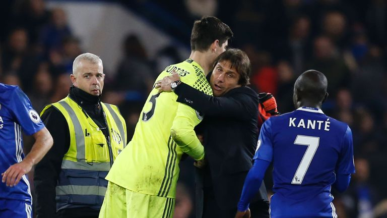 Courtois (left) embraces manager Antonio Conte