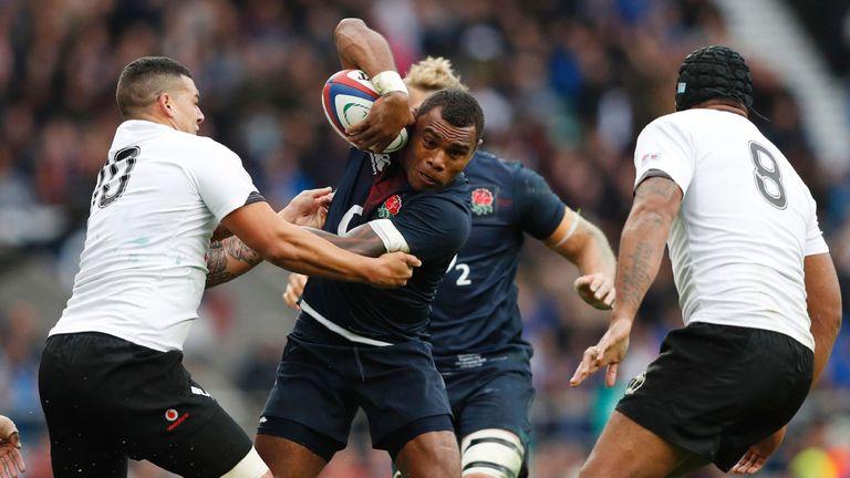 England's Semesa Rokoduguni (C) is tackled by Fiji's fly-half Josh Matavesi