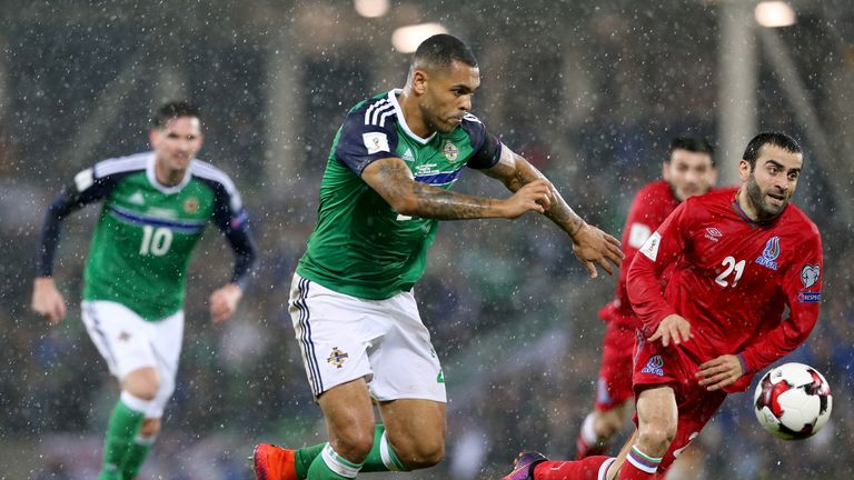 Josh Magennis (centre) challenges for the ball