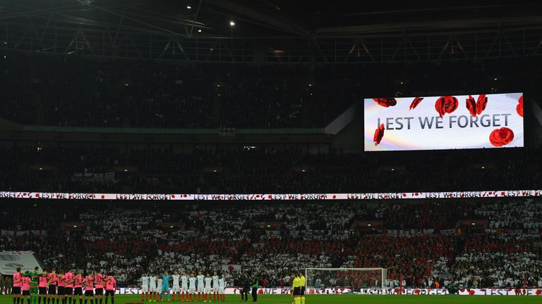 Players, officials and fans observe a silence in remembrance of Armistice Day at Wembley
