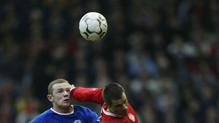 Carragher battles for possession with Wayne Rooney