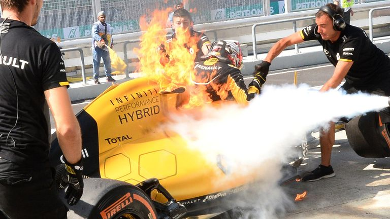 A fire from Kevin Magnussen's Renault car is extinguished in the Sepang pitlane - Pictures from Sutton Images