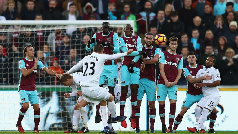 Gylfi Sigurdsson strikes a free kick over a wall of West Ham players