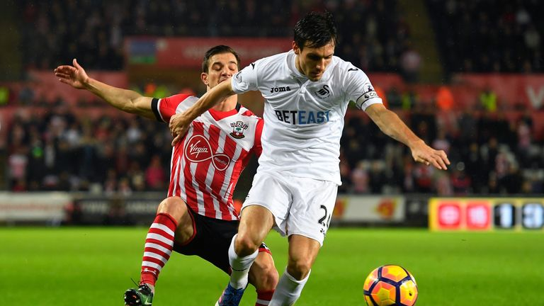 Jack Cork of Swansea City (right) controls the ball under pressure of Cedric Soares of Southampton