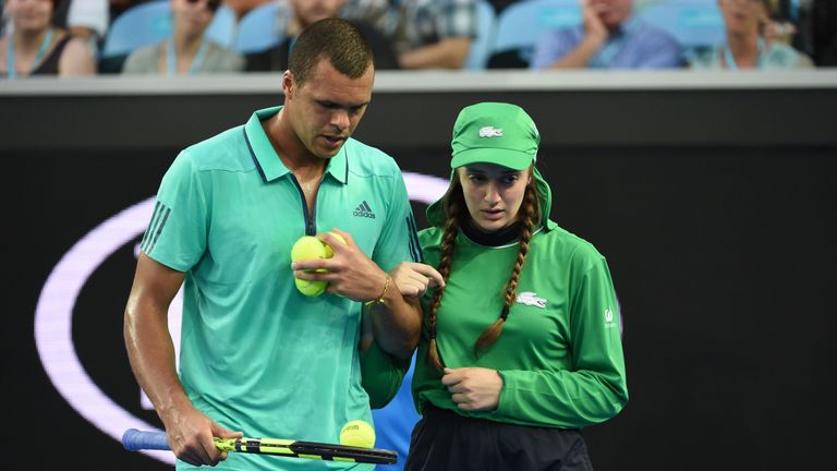 Jo-Wilfried Tsonga escorts an unwell ball girl from the court during his singles match against Omar Jasika at the Australian Open