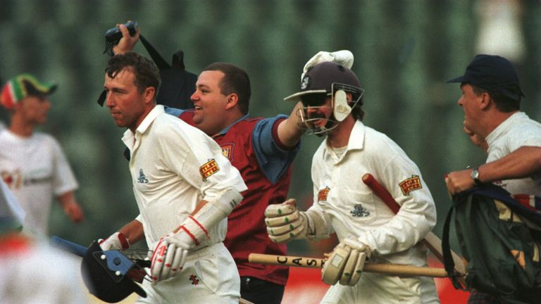 A triumphant Atherton (L) and Jack Russell race from the field in Johannesburg after saving the 1995 Test