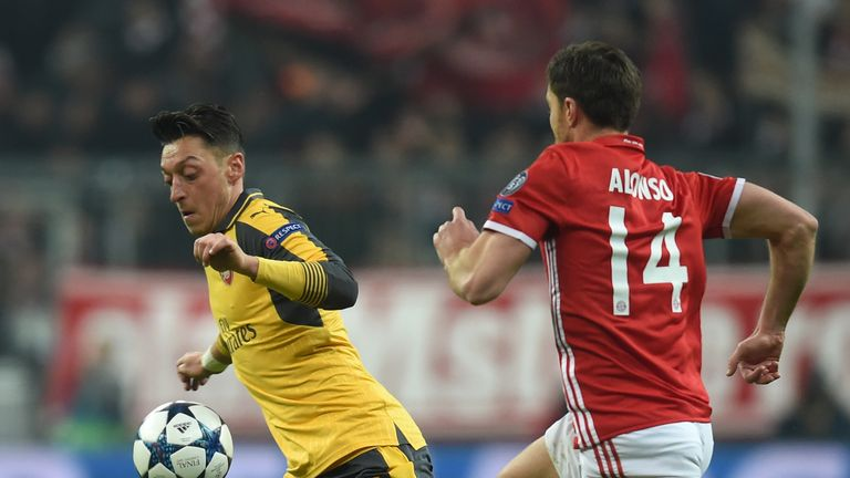Mesut Ozil (left) takes on Bayern Munich's Xabi Alonso