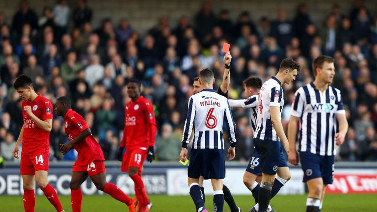 Jake Cooper of Millwall (CR) is shown a red card by referee Craig Pawson