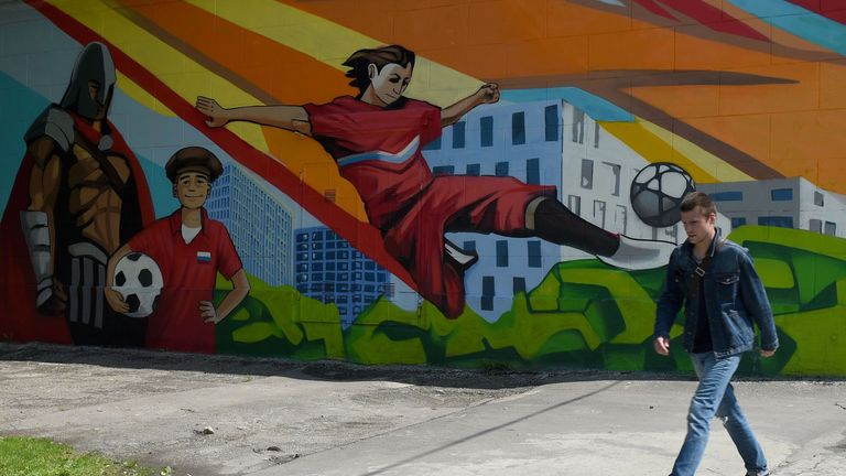 A man walks by a football mural on the wall of a Moscow building