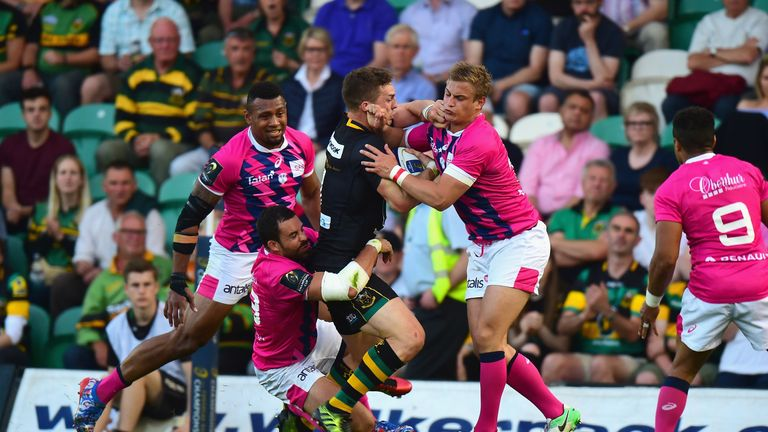 George North  is tackled by Stade Francais duo Geoffrey Doumayrou and Jules Plisson (right)