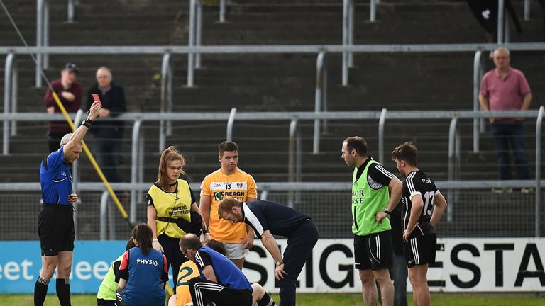 Referee Fergal Kelly shows a red card to Jack Dowling of Antrim, hidden
