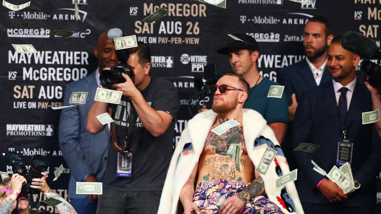 McGregor looks on as money rains down during the Floyd Mayweather Jr v Conor McGregor World Press Tour