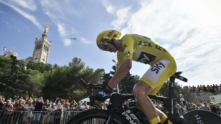 Froome, wearing the overall leader's yellow jersey, rides past the Notre-Dame de la Garde basilica (L)