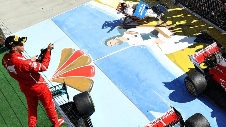 Fernando Alonso takes a break as Vettel celebrates his win