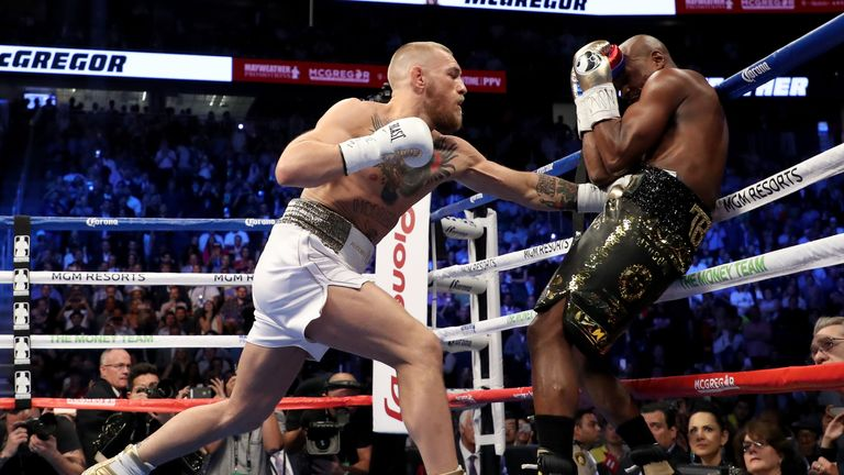 McGregor throws a punch at Mayweather in the opening round