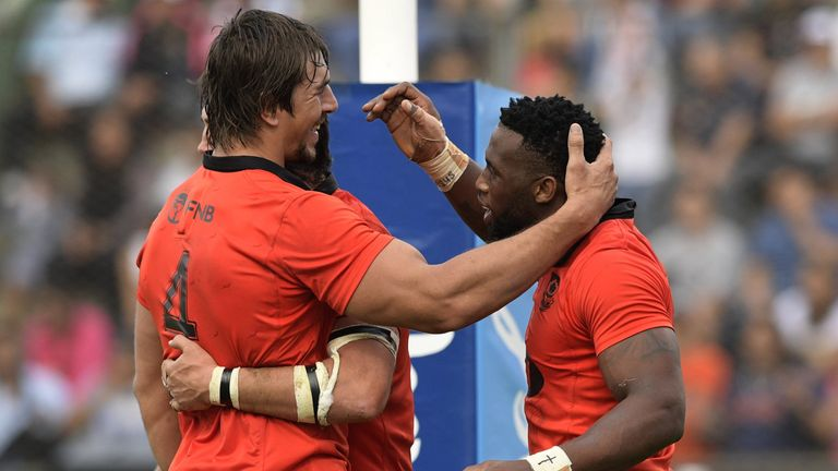 South Africa's flanker Siya Kolisi (R) celebrates with lock Eben Etzebeth (L) and  lock Franco Mostert after scoring his team's third try