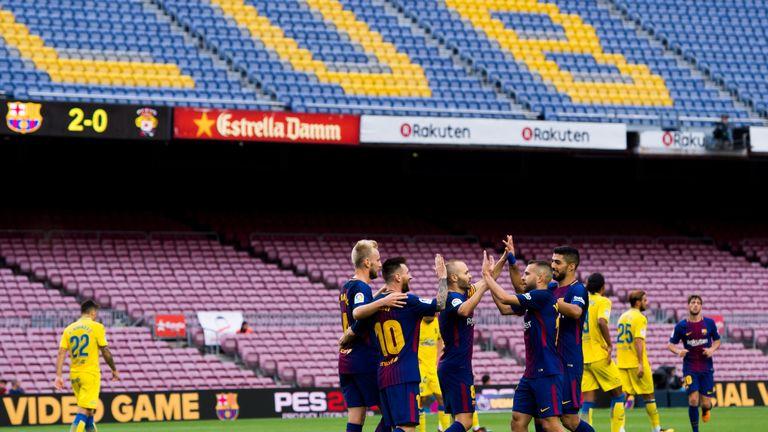 Lionel Messi celebrates with team-mates inside an empty Nou Camp against Las Palmas